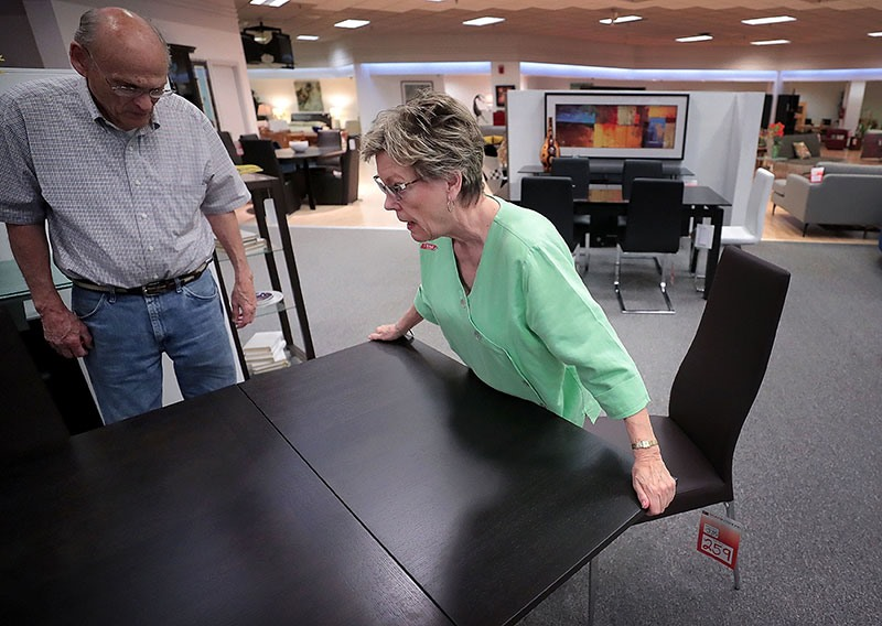 Scan Interiors Employee Judy Tomlinson Right Shows Mike Cabe How A Retractable Table Extension Works At The East Memphis Furniture On Thursday